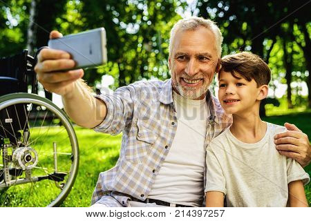 The boy and his grandfather are sitting in the park on a picnic. Boy is holding a smartphone and making selfy with his grandfather