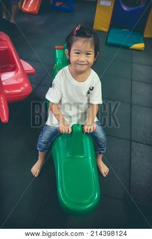 Cute asian child having fun and looking at camera while feeling happy at children indoor playground. Asian girl smiling and sitting on green plastic seesaw. Vintage film filter effect.