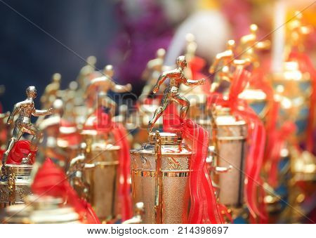 Athletes trophy cup awards with a red ribbon. Group of runner trophy on the blue background.