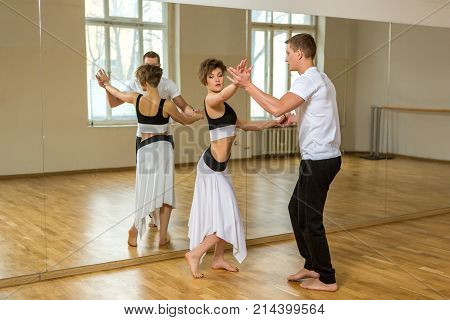 beautiful couple dancing tango. young woman in black and white dress and man in sport clothes practicing in dancing studio mirror room. copy space.