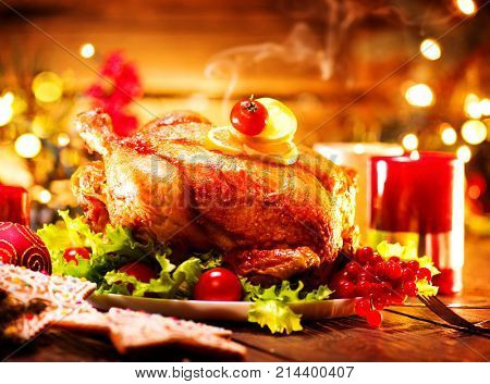 Christmas Dinner. Roasted chicken. Winter Holiday table served, decorated with candles. Roast turkey over wooden background with christmas tree, table setting