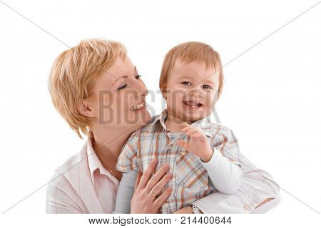 Mother and baby embracing in affectionate moment. Copyspace above.
