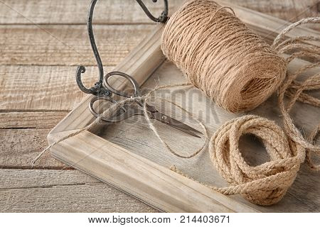 Tray with hank of hemp twine and rope on wooden background