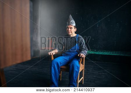 Man in tinfoil hat sits in chair, paranoia concept