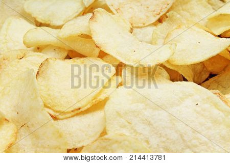 Chips pattern. Yellow salted potato chips as background. Chips texture studio food photo.
