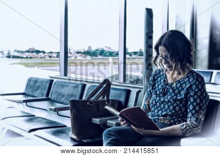 Feeling at home away from home - Brazilian woman reading a book at the airport