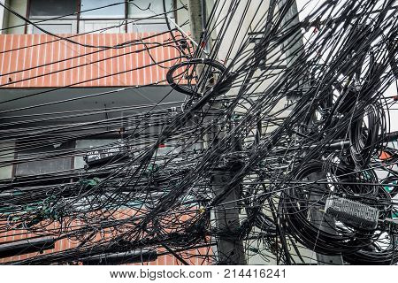 Messy wires attached to the electric pole, the chaos of cables and wires on an electric pole in Bangkok, Thailand, concept of electricity