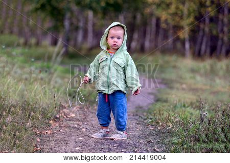 A one-and-a half year old girl on a path in a park with a rope in her hand. The girl looks aside. Interested inquiring glance.