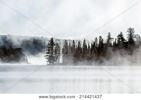 Lake of two rivers in algonquin national park ontario canada sunset sunrise with fog foggy mystical atmosphere background