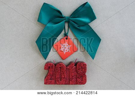Green silk ribbon bow and 2018 year red candle. Christmas holiday ornaments on rustic background. Top view
