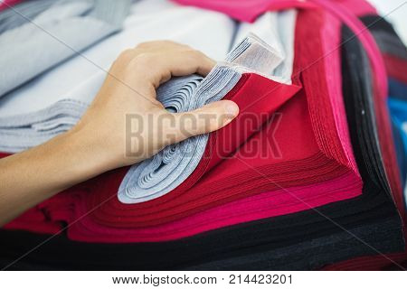 Woman choosing fabric colors. Concept: material, fabric, manufacture, garment factory new samples of fabrics