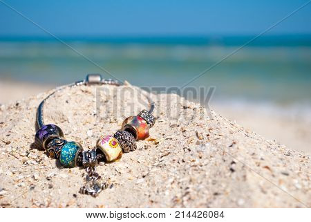 beautiful female bracelet decoration jewelry with large beads and rhinestones lies on the yellow sand summer beach sea shore blue sky vacation vacation weekend