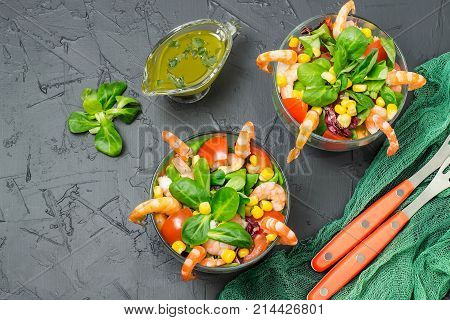 Fresh salad with shrimps tomatoes sweet pepper corn and green salad leaves. Served with vinaigrette sauce. Concept of diet and healthy food. Glass bowls with salad green gauze napkin and forks