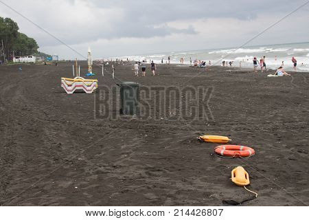 red plastic floatation rescue devices and sunbeds on beach. cloudy weather overcast. safety vacation rescue tool