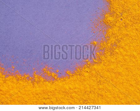 Turmeric Powder or Curcuma longa on violet background. Top view. Copy space for text.
