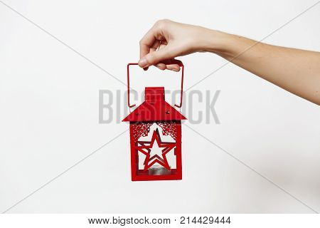 Female Hand Holding Red Vintage Christmas Lantern With Candlestick Isolated On White Background. New