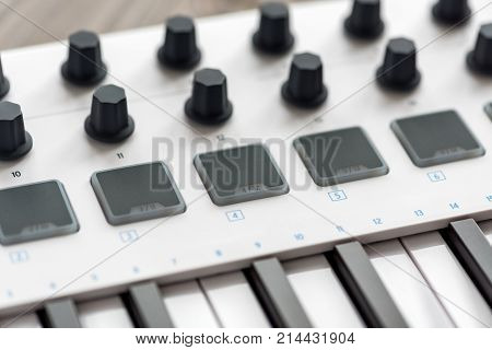 White MIDI keyboard with pads and faders