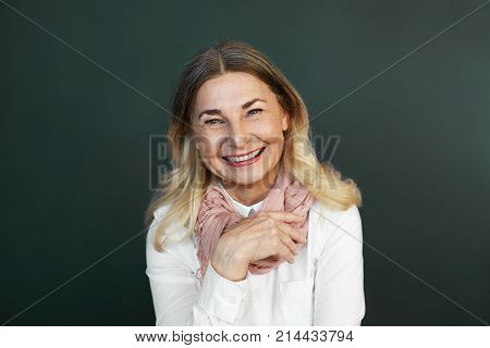 Isolated shot of joyful happy beautiful European grandmother in good mood grinning broadly showing her healthy straight teeth at camera while talking to her grandson laughing at his jokes