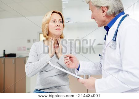 Sick mid-aged female complaining about sore throat to her doctor