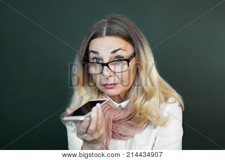 Charming elderly woman in rectangular black rimmed eyewear using voice recognition function on cell phone. Modern senior female holding electronic gadget sending vocal message via online messenger