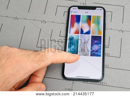 PARIS FRANCE - NOV 9 2017: Male hand touch selecting New Apple iPhone X 10 smartphone screen after unboxing and selecting live wallpaper