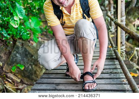 Tourist With A Backpack Zips Up Sandals On The Trail