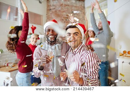 Laughing intercultural guys with champagne enjoying xmas party with friends