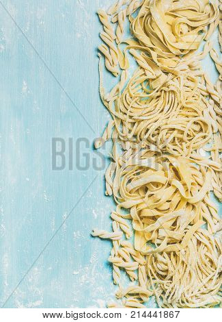 Various homemade fresh uncooked Italian pasta with flour on blue wooden background, top view, copy space,