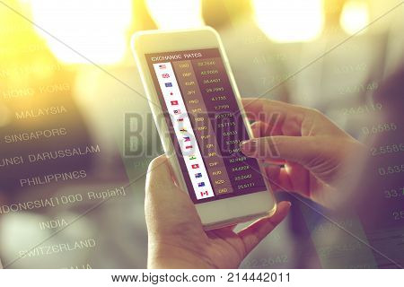 hand holding smartphone for checking exchange rates by currency application on fight to travel double exposure with currency exchange rates background