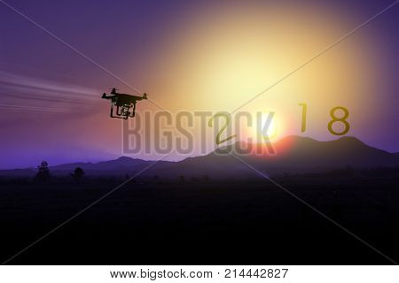 silhouette of drone flying to the mountain view at sunset. fly to newyear 2018