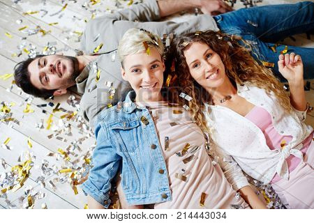 Two happy girls and guy lying on the floor after dance party in confetti