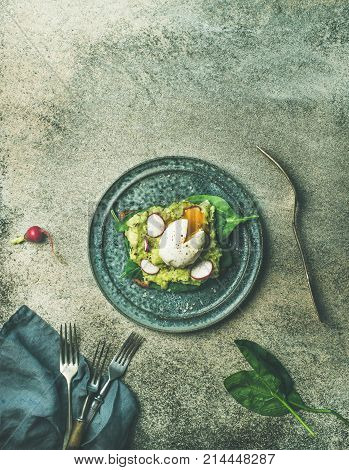 Healthy vegetarian breakfast flat-lay. Wholegrain toast with avocado, spinach and poached egg on plate over grey concrete background, top view, copy space. Clean eating, weight loss, diet food concept