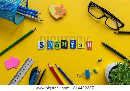 SPANISH made with carved letters on yellow desk with office or school supplies, stationery. Concept of Spanish language courses.