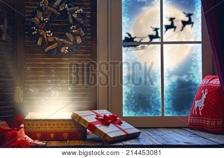 Merry Christmas! Magic gift box on the sill. Window decorated for holidays. Santa Claus flying in his sleigh against moon sky.