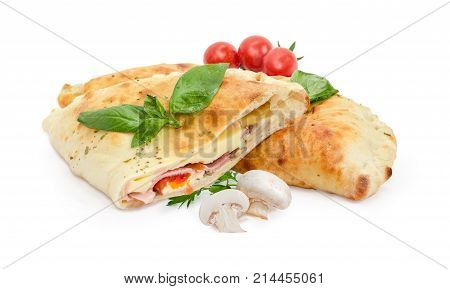 Half and whole of the baked calzone - closed type of pizza that is folded in half decorated with basil and parsley twigs raw mushrooms and cherry tomatoes on a white background