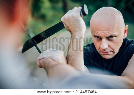 Martial arts instructor demonstrates machete fighting concept. Long knife weapon training. Demonstration with a real metal machete