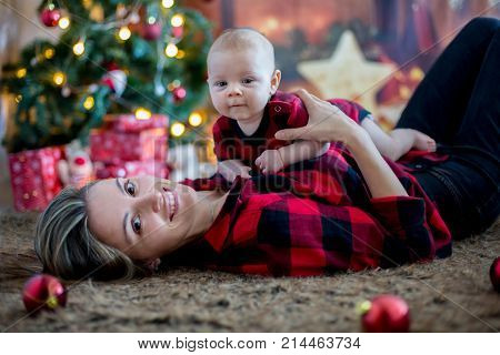 Happy Young Mother And Her Son Playing At Home During Christmas Holidays