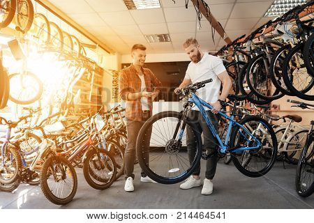 A seller at a bicycle store helps a young buyer choose a new mountain bike. A man with a beard and a client looks carefully at the goods. Around them there are many parts for bicycles.