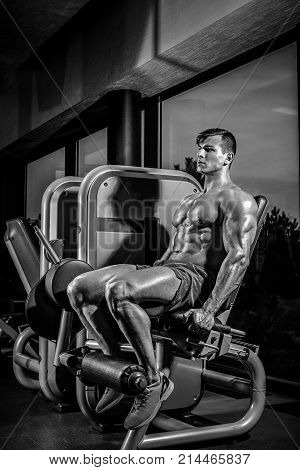 Leg Exercises - Man Doing Leg With Machine In Gym. Sexy muscular man posing in gym. Black and white