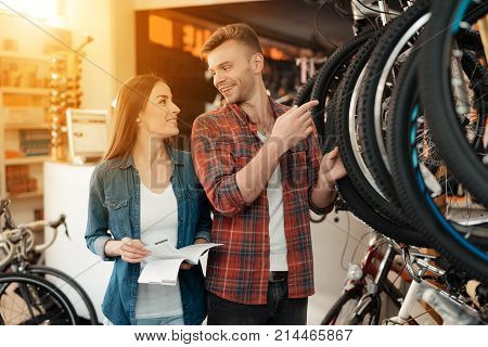 A young couple came to the bicycle shop to choose a new bicycle. A man and a woman look attentively at different bicycles and details. The girl is holding the instruction.