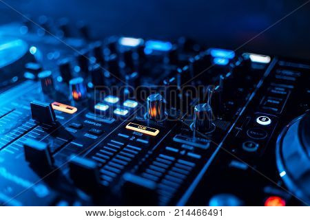 buttons and volume levels and mixing music on professional Board DJ to play music
