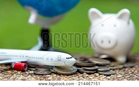 Tourist travel planning for saving money in the piggy for travel airplane with around the world. Travel and Saving Concept select focus