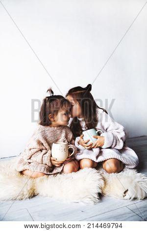 little girls in a sweater drink tea