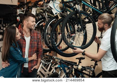 A young man with a beard shows a man and a woman a wheel from a bicycle in a bicycle shop. A young couple came to buy a bicycle. They are happy about this.