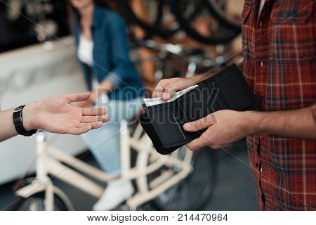 A man gives money to another man. They are in the store. The buyer has wallet with cash in his hand. He buys a bicycle.