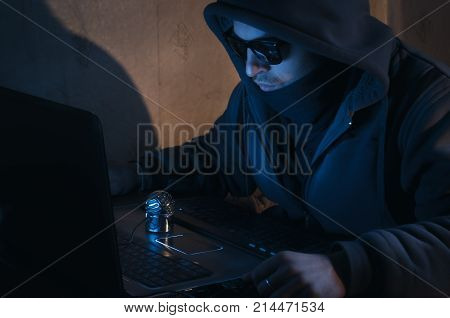hacker in a hood in a dark room, the intruder breaks into a system, the concept of web crimes