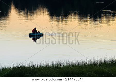 A Silhouette Of Man Fly Fishing On A Quiet Summer Evening