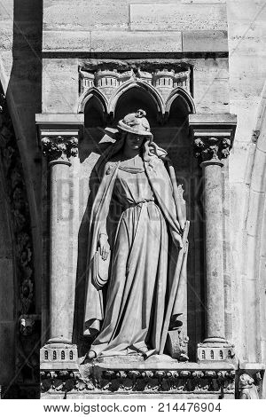 Architectural details of the facade of catholic cathedral Notre-Dame de Paris in black and white. Notre-Dame cathedrall is built in French Gothic architecture. Paris France