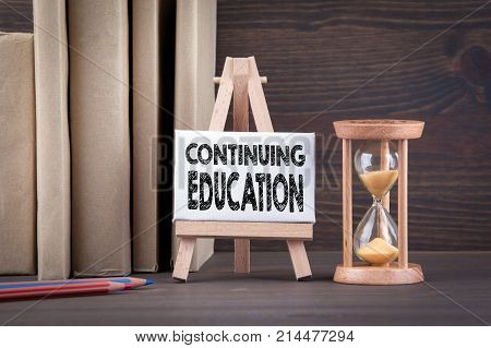 Continuing Education concept. Sandglass, hourglass or egg timer on wooden table showing the last second or last minute or time out