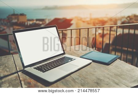 Modern laptop with blank screen mockup and huge trackpad on the wooden table next to tablet pc; netbook with empty white screen template near digital tablet on balcony workspace with blurred cityscape